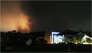 De la fumée rose s'échappe de bâtiments suite à des bombardements aériens à Tripoli